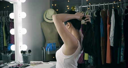 performer : slow motion of fashionable young asian woman model tying her beautiful long black hair in ponytail.