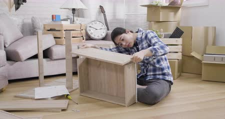 errado : alone female human is assembling new furniture installing parts and fixing in light living room. Stock Footage