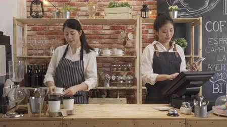 Two restaurant owners wear apron working in counter.