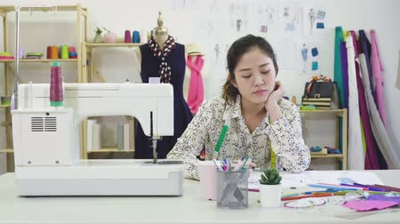 slow motion of thoughtful creative female fashion designer drawing sketch of dress in workshop. Dostupné videozáznamy