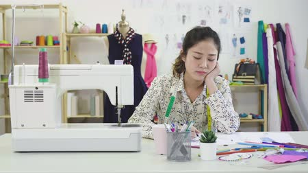 Beautiful fashion designer is drawing clothing sketches for her new clothes collection.