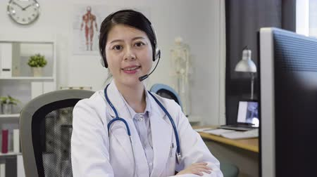 slow motion smiling female doctor chatting to patient on headset as she sitting in clinic and giving friendly advice.