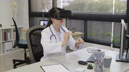 slow motion doctor woman watching computed tomography shot using vr headset sitting at desk in hospital office.