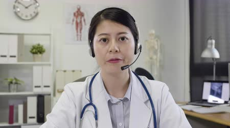 beautiful asian doctor consults patient on the internet having video phone call in hospital.