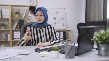 islam business woman using computer sending email and another chinese designer coworker checking document in back.