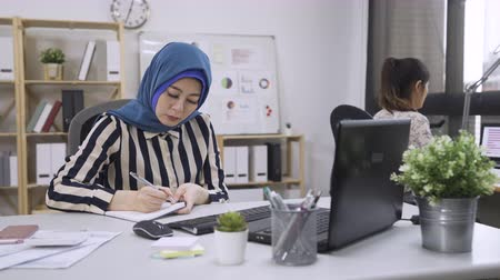 confident muslim businesswoman wearing blue with hijab working and writing in bright office.