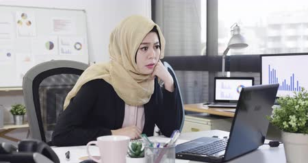 serious concentrated islam businesswoman in suit working at laptop and sitting at table while looking computer screen and hand on chin. thoughtful confused frowning muslim office lady with problem
