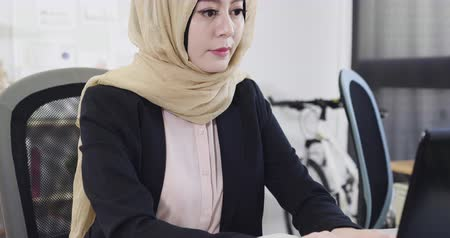 slow motion young female muslim entrepreneur working sitting at desk typing on laptop computer in office view from low to above. elegant arabic start up businesswoman manager work on notebook pc.