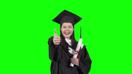 Happy graduate. asian woman college student in bachelor gown with diploma showing thumbs up face camera smiling standing on green background. happy successful university girl in traditional uniform. Dostupné videozáznamy