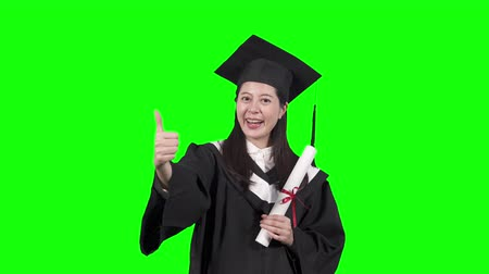 graduation asian girl holding her diploma scroll with pride. young chinese woman college student face looking camera smiling attractive showing thumb up hand gesture chroma key. happy successful.