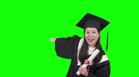 young asian woman university student in graduate uniform waving hands say hi introducing talking showing to camera smiling cheerful. beautiful college girl holding diploma sending kiss chroma key.