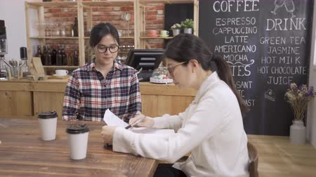 Young female candidate listening at interviewer explain company firm offers attractive employee benefits at job interview. beautiful college girl fresh graduate seeking job meeting in cafe bar.