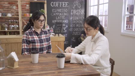 Young attractive girl applicant giving resume to manager job interview. asian woman interviewer asking question talking while reading cv paper document in cafe bar. two female meeting in coffee shop