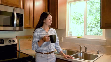 young asian local woman at home leaning on kitchen table by sink hold cup of coffee enjoy morning time before work.