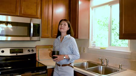Beautiful young asian woman drinking coffee in wood kitchen at home. Wideo