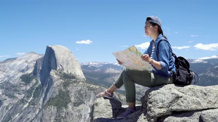 backpacker tourist in hat sit with map on rock at top of mountain.