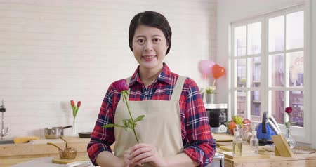 romantic asian woman holding red rose in hands at wooden kitchen.