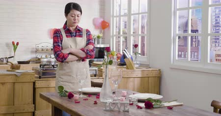 women unsatisfied while setting up table for romantic valentine day dinner at home.
