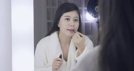 evsahibi : slow motion beautiful young asian japanese woman applying makeup in dressing room.
