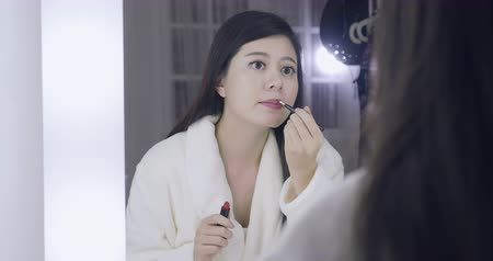 evsahibi : beautiful asian woman with dark hair applying makeup in dressing room.