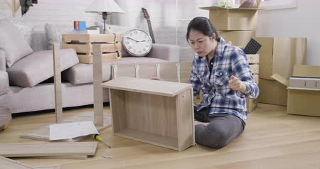 slow motion of frustrated asian woman reading instruction assembly furniture sitting in apartment living room. Vídeos