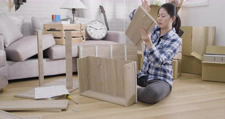 slow motion frowning woman assembling furniture in living room. Vídeos