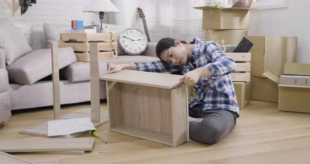 хмурый : young unhappy woman assembling shelf at home with confused emotion sitting on wooden floor in living room.