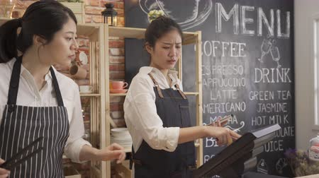 çözme : two asian women wearing apron working as barista in cafe shop counter. Stok Video