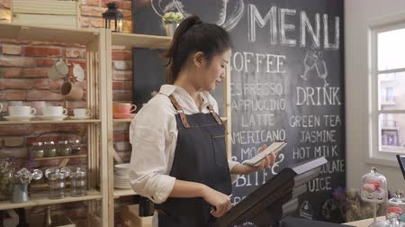 female barista smiling working with tablet behind counter in cafe shop.