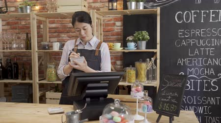 Beautiful asian woman barista in apron writing down order on note and entering on tablet at bar counter.