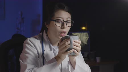 young female medical nurse drinking cup of coffee at dark clinic