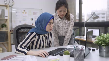 muslim leader : strict malay female boss scolding young member of chinese woman staff or subordinate sitting in front of computer screen. Stock Footage
