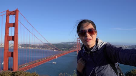 Young asian woman video chats on beautiful landscape golden gate bridge in background and showing sea.