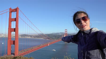 . Happy asian tourist girl waving at webcam on mobile phone camera sharing summer travel vacation adventure in san francisco golden gate bridge.