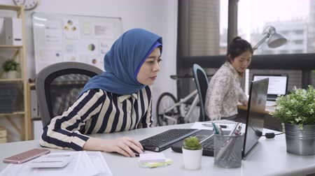 muslim woman manager talking to new hire chinese lady employee in coworking space.
