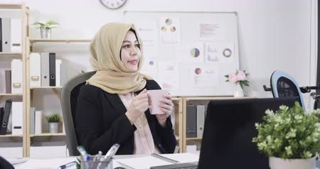 young start up arabic businesswoman relax holding cup of tea while done project.