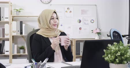 young smiling arabic office lady manager with cup tea after typing laptop.