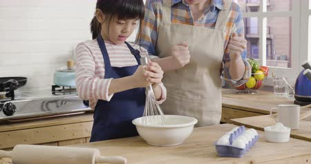 slow motion chinese little girl and beautiful mother apron smiling while baking at home. Dostupné videozáznamy