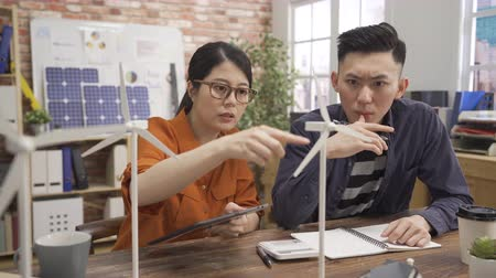 small pen : two young asian male and female engineer explaining basics of wind power station using tablet.