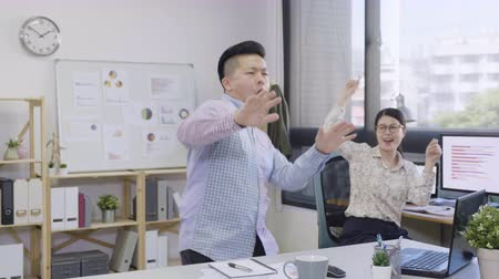 slow motion excited asian small business company employees coworker dancing in office.
