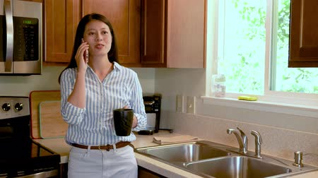 hot beverage : Young asian smiling woman using smart phone leaning at kitchen table with coffee mug.