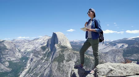 fele olyan hosszú : asian woman hiker standing on mountain top with backpack and map in her hands to search for new adventures in nature trail forest in yosemite.