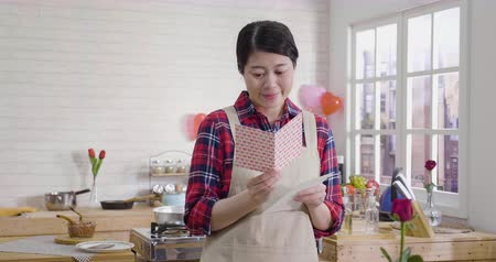 attractive asian housewife reading valentine card with full of hearts and looking sweet. Wideo