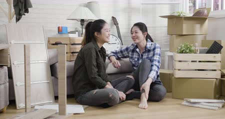 Young family asian sisters relax while assembling furniture at new house. Vídeos