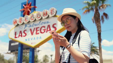 Beautiful young asian woman tourist standing outdoor by welcome las vegas sign and surfing internet on mobile phone. girl traveler looks around and continued to search direction on map in smartphone