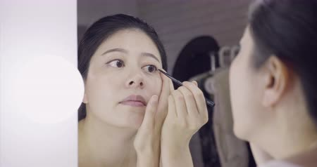 beautiful young dark haired asian woman entertainer using black eyeliner pen while applying makeup on face. Vídeos