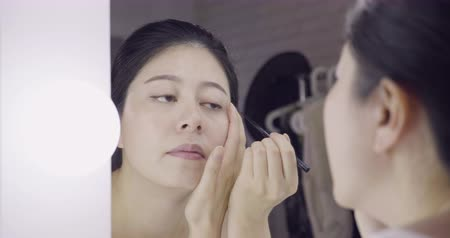 celebrities : Eyeliner eye makeup beauty care concept. Asian girl artist putting eye liner pencil on eyes looking in mirror at vanity table. Stock Footage