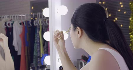 vanity : slow movement side view of beautiful young woman performer make up at dressing table before go on stage. Stock Footage