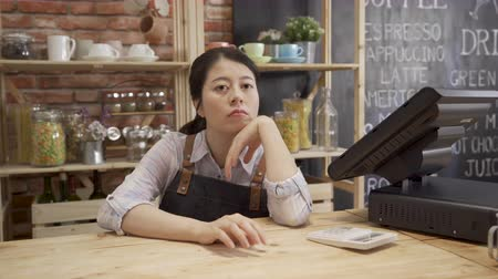 small startup business owner depressed while economy in slump. cafe store waitress with hand on chin in counter using finger drumming on wood table. Vídeos