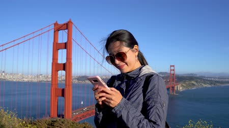 happy smiling asian woman backpacker standing on mountain peak with golden gate bridge in background san francisco usa. Vídeos